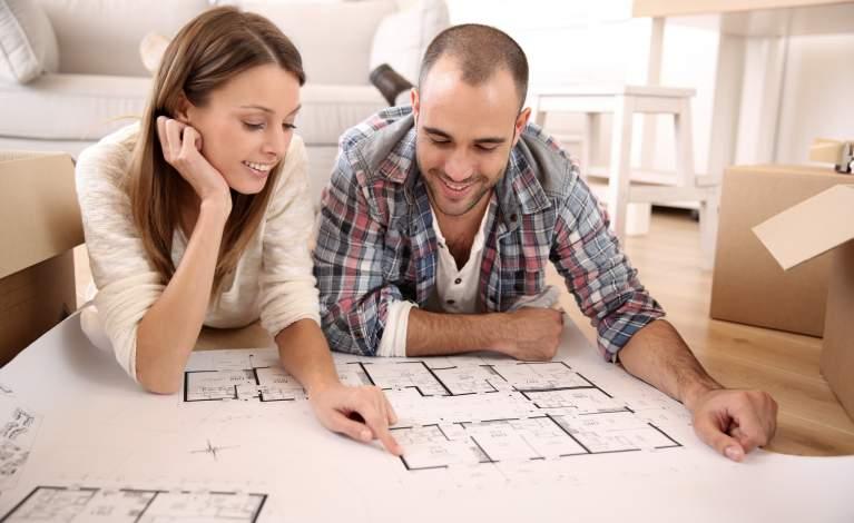 Couple devant un plan d'architecte